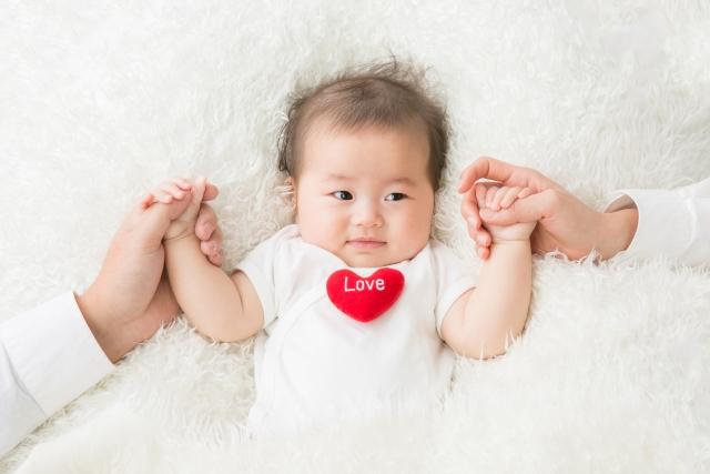 手を繋ぐ赤ちゃんと親