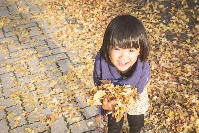 落ち葉を持つ子供